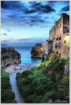 Polignano al Mare, Italy. Polignano a Mare (Peghegnéne in Bari dialect) is a town and comune in the province of Bari, Apulia, southern Italy, located on the Adriatic Sea.