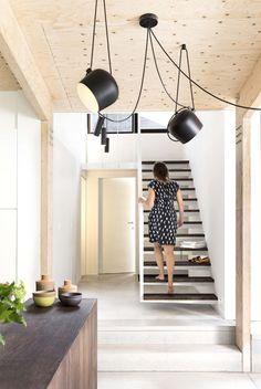 FLOS AIM pendant lights bring a modern touch to this simple interior with wooden a concrete floor, a wooden ceiling and white walls.