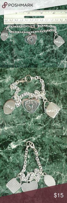 Mother's charm bracelet Perfect for the mother of a newborn baby! Silverstone bracelet with a lobster claw clasp. Includes 3 charms, 1 mug that says BSBY, a heart with tiny footprints and an oval shape that says LOVE.  This item is New, but did not come with tags. It was just wrapped in plastic and hanging around a vase. FTD Jewelry Bracelets