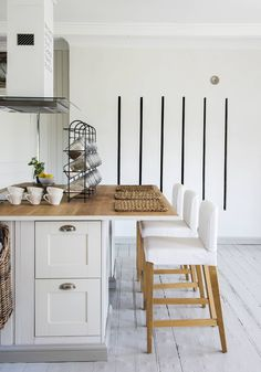 Riviuunin raoista hehkuu lämpöä isoon tupaan. Keittiön saarekkeeseen tilattiin ovet puusepältä, muuten Reijo rakensi sen itse. Helat ostettiin Rakennusapteekista. Vanhassa karkki-telineessä ovat nyt kuiva-aineet kauniisti esillä. Korkeat tuolit ovat Ikeasta. Ovet, Living Room, Table, Kitchens, House, Furniture, Home Decor, Decoration Home, Home