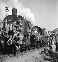 German refugees and displaced persons crowding every square inch of a train leaving Berlin after the war's end. 1945.