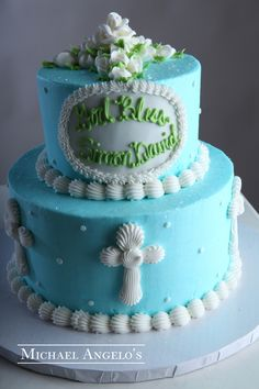 Green Monogram #39Religious This blue buttercream design is accented with whit crosses and polka dots surrouning the entire cake. A monogram plaque is placed on the top tier along with a bed of roses in the shape of a cross