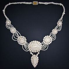 A ravishing and romantic antique necklace composed of a zillion (count 'em!) tiny seed pearls intricately woven atop eight graduated mother-of-pearl plaques. A delightful citrine clasp completes this exemplary and delicate delight.