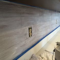 DIY Backsplash out of oak peel and stick vinyl plank flooring. Dry brush painted and nailed to look like shiplap.