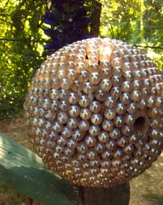 Peach Dragon egg, from www.karentiede.com/articles .  Note thumbhole--it's a bowling ball underneath.  Mounted on rebar which has been drilled into the newel post.  7 or 9 bags of marbles from the hobby store; silicon caulk.