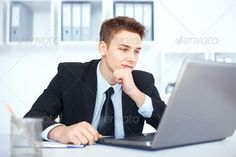 Young businessman working on laptop in office ...  adult, beauty, black, bright, business, businessman, busy, career, caucasian, cheerful, communication, computer, confidence, desk, folder, hand, handsome, human, indoors, internet, laptop, looking, male, man, manager, necktie, notebook, office, one, only, pensive, people, person, portrait, positivity, professional, shirt, sitting, smiling, student, success, suit, table, technology, thinking, using, white, working, workplace, young
