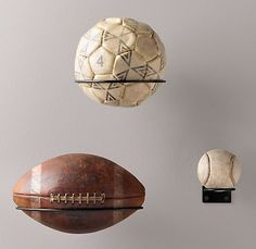 from restoration hardware. wall holders for sport balls; football, soccer, baseball. cute for a boys room or game room