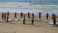 Group taking surf lesson on beach