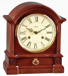 "Hollins Mantel Clock Free Shipping! 30-Day Money-Back Guarantee! 3-Year Manufacturer Warranty!  This barrister style table clock features a cherry finish with fluted molding, starburst carvings, brass handled drawer, ivory dial and black Roman numerals. Mechanical strike movement. 8 days power reserve. Half hour strike.  Hand assembled. Includes 3-year manufacturer warranty.   Hollins Mantel Clock Dimensions: L: 10"", W: 8"", D: 4.5"""