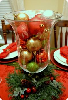 ornaments in hurricane glass with greenery