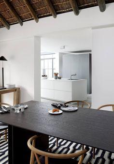 Kontrastreicher Blickwinkel: Der warme, reetgedeckte Essbereich eines Anwesens in Kapstadt und der puristische Küchenbereich finden ihre Verbindung im einheitlich klaren, schlichten Stil des bulthaup c3 Tischs und der bulhaup b3 Kücheninsel.