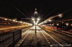 Het station in Wijchen op een koude donkere winteravond met links en rechts sneltreinen die voorbij flitsen.