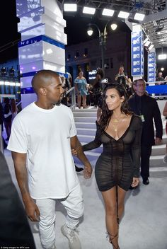 Lean on me: Kim takes hold of her husband as the pair head inside the venue