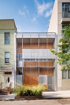 Courtyard House by Philippe Baumann. A grid of hinged metal shutters form a privacy screen across the windows of this terraced house in New York that architect Philippe Baumann designed for himself and his partner.