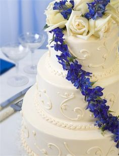 Three tier wedding cake with blue flowers Love this cake but with plum colored flowers
