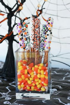 """""""Dipped Pretzel Rods are instantly transformed into """"Witches Wands"""" with a little Halloween pizzazz! I sometimes have a hard time finding them in stores, so you can get them here if you find yourself in the same boat. Put them in containers with candy corns to hold them up. The little mini buckets pictured are from the Target dollar section. SO cute!"""""""