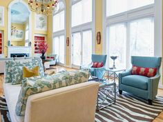 This open, cathedral-style living room features buttery yellow paint, a zebra-print rug, turquoise arm chairs and pops of hot pink throughout.