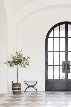 Stunning entryway with large black iron arched front doors #entry #archeddoors