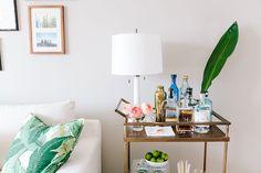 bar cart styling + banana leaf pillow | Ashley Kane's San Francisco Apartment Tour #theeverygirl
