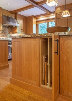 Partitioned cabinet on prep island for trays, cutting boards, cookie sheets.