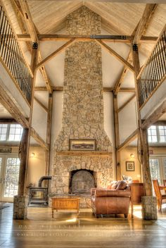 This would be my number one on my dream house when it gets built {Rustic living area with a two-story fireplace and beautiful beams}