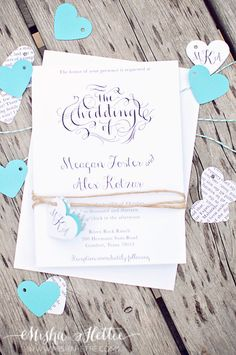 DIY wedding invitations wrapped in twine with heart cutouts