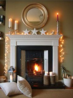mantlepiece decorated with candles and warm white fairy lights