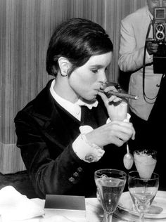 Actress Geraldine Chaplin smokes a cigar at a table during the Cannes Film Festival, May 2, 1967, in France. (Photo by RDA/Hulton Archive/Getty Images)