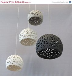 This pendant light is hand made of white, grey and black stoneware. You may choose to have the sheres all in the same color. I use a