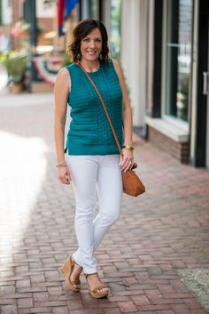 This gorgeous teal sleeveless sweater outfit with white jeans and cognac accessories is perfect for summer, and the sweater is also a great transition piece for fall.