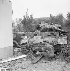 """Normandy 1944 - A British soldiers """"covers"""" beside a knocked out German Panzer III."""