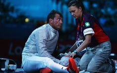 Luigi Tarantino of Italy sits injured during the men's sabre individual fencing round of 32 match against Max Hartung of Germany