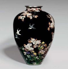 AN IMPORTANT CLOISONNÉ VASE  SIGNED ON A SILVER TABLET KYOTO NAMIKAWA, MEIJI PERIOD (LATE 19TH CENTURY) Worked in various thicknesses of silver wire and coloured enamels on a black ground with birds perched or in flight amongst cherry blossom above irises and daisies, silver mounts 18.5cm. high