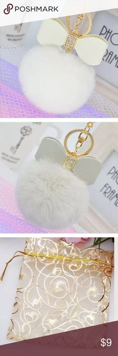 White faux fur pom pom keychain with bow Brand new. ‼️Please ❌trade and ❌offers. Price is firm unless bundled.‼️Comes in a beautiful golden pouch. Elegant Jewelry Accessories Key & Card Holders