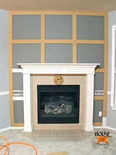 A dramatic fireplace makeover {white moulding & black mantel}