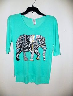 Juniors turquoise short sleeved top with an elephant graphic. There is a slit down each side of the top. We love the designs in the elephant, and the color is gorgeous. #scottsmarketplace