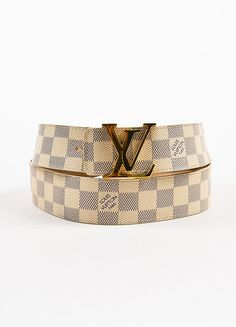 "Cream and navy damier print coated canvas belt circa 2009. ""LOUIS VUITTON PARIS"" on print. Shiny gold toned 'LV' buckle with post closure and five notch options. Nubuck leather lining. Retails for $49"