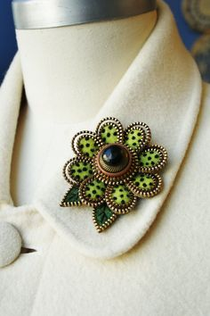 """Lime green felt and zipper brooch.This brooch has been made from recycled wool sweater felt. Outside of the petals are enveloped with two layers of brass zipper. Further embellished with three stacked vintage buttons at the very center. There are two embroidered leaves on the outside of the flower. The aprox. dimensions of the brooch are 2 1/2"""""""" x 2 1/2"""". It is firm & a medium weight brooch, for a jacket or coat."""