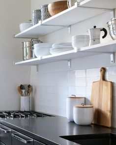 """""""I also knew I wanted open upper shelves so everything could be right at my fingertips."""" The shelf brackets are the Dolle Belt Metal Bracket in stainless steel from Blue Stone Shelves. The drawer handles are Rejuvenation's Larkin in chrome. The backsplash is ceramic tile from Tile Bar (Lancaster 3x12 in Bianco). The plates are Crate"""