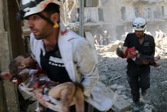 """The White Helmets carry the bodies of children following a reported bombardment with explosive-packed """"barrel bombs"""" by Syrian government forces in the al-Mowasalat neighborhood of the northern Syrian city of Aleppo on April 27, 2014."""