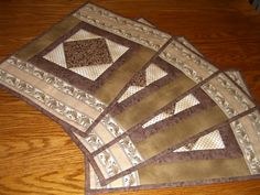 These patchwork placemats are made from cocoa brown prints. Each one measures 13 1/2 by 18 1/2. Back is solid muslin. Set of four.