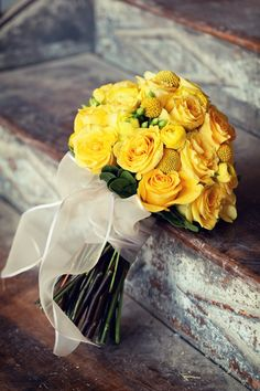 Pretty all yellow mix of roses, rananculus, Craspedia and Hypericum berry.