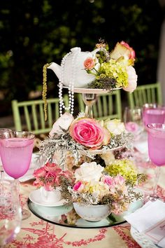 elaborate bridal shower centerpiece with roses, tea cups, and tea pots on vintage tiered stand