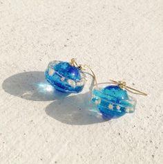 海の惑星をイメージして作りました。星の砂や琉球ガラス、銀箔青ラメなどを使っています。レジン作品です。約2㎝です。樹脂製フック、イヤリングにも変更可能です。ご記...|ハンドメイド、手作り、手仕事品の通販・販売・購入ならCreema。