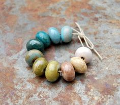 Hand formed ceramic pebble beads in blues and browns… Gaea.cc Ceramic Bead and Art Studio Blog: 999 Apparently.