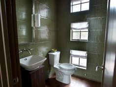The adjacent powder room continues the home's rustic-chic design focus, with walls clad from floor to ceiling in rich green mosaic tile.