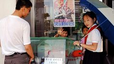 My visit to North Korea coincided with hot summer weather. Here, people queue in front of an ice cream vendor in Pyongyang. The ice cream consists of only water, milk and sugar, but demand was high on that warm day. Behind the stall, a propaganda poster hangs on the window.