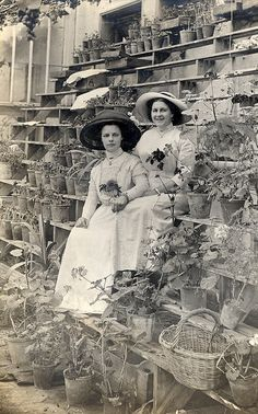 Two Edwardian young ladies among the pots