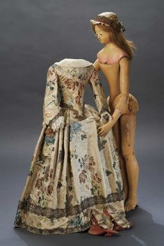 Georgian wooden Doll & gown, 18thC Northern Italy. Original jointed body with well-shaped elongated legs. Hands restored. Human hair wig. Gown woven silk with homespun lining, bone-shaped bodice with back lacing closure, sleeves designed open at the back with silk tie ribbons, gilt metallic borders, along with original under-blouse/chemise,petticoat,hand-woven warm stockings, hand-stitched sandals with gemstone accents and silk (matching gown) soles. Theriault's Antique Doll Auctions