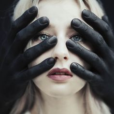 Girl and painted black hands.